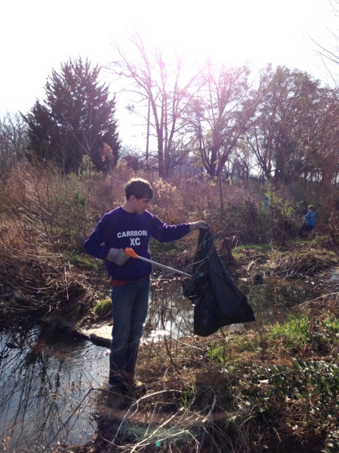 Kol Haskalah member picking up trash along a creak in Liberty Park